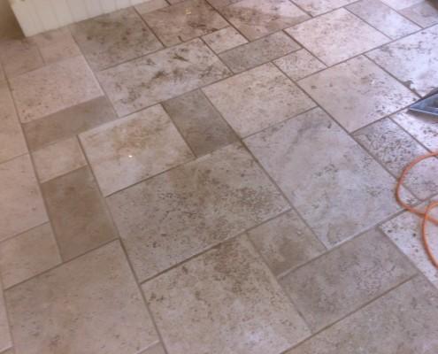 Travertine kitchen floor being cleaned